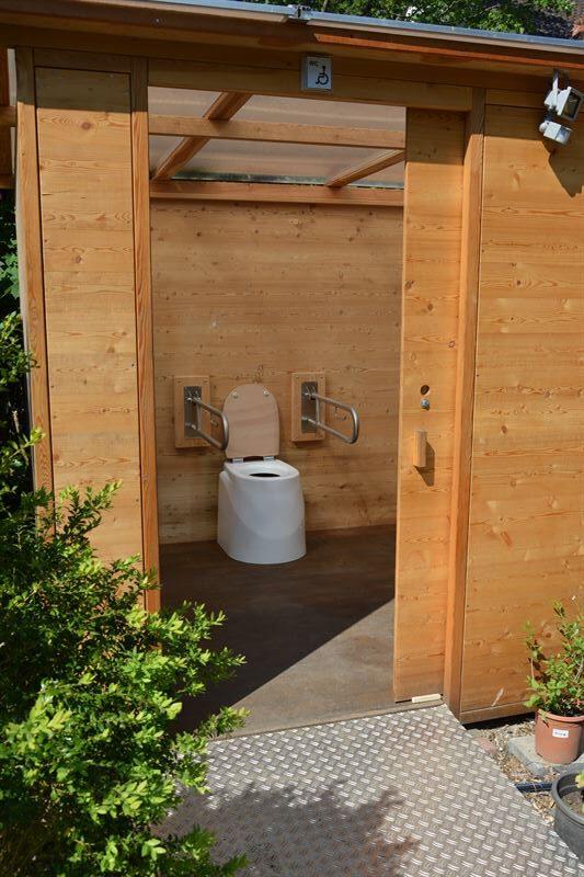 Toilette WALD barrierefrei nach DIN mit Ecodomeo. Blick in die Kabine. 90 cm links und rechts vom Sitz, Stützklappgriffe links und rechts.
