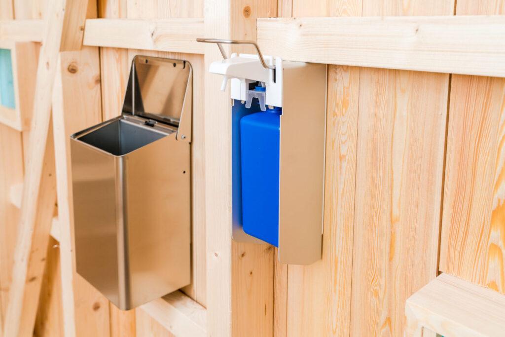 Trockentoilette KUBUS - öffentliche Toilette aus Lärchenholz mit Toilettensystem ECODOMEO - Wandmülleimer aus Edelstahl und Handgelspender
