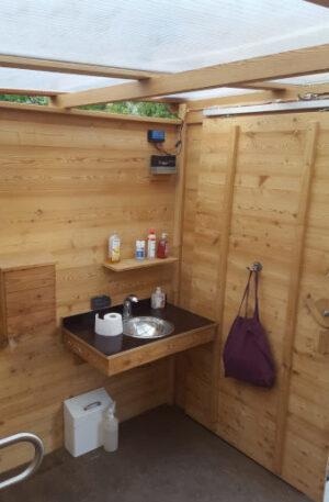 Handwaschbecken in Toilette 'WALD BARRIEREFREI nach DIN'. Handwaschbecken-Platte aus Siebdruckplatte und Lärche Vollholz
