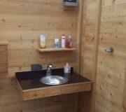 Optionales Handwaschbecken für barrierefreie Toilette nach DIN. Mit Edelstahlbecken und Wasserspararmatur mit IR-Sensor.